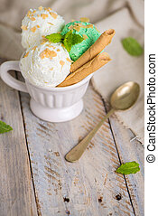 Vanilla and mint ice cream in cup on wooden vintage style...