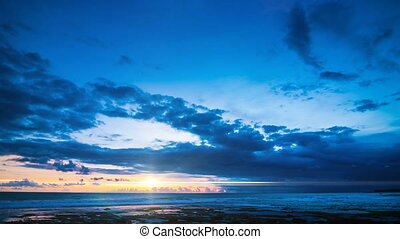 Fiery sunset in the blue sky over the ocean time lapse