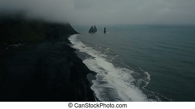 Aerial view of the black volcanic beach in Iceland and troll...
