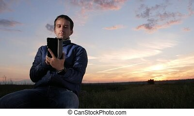 A young man sits at sunset and checks the messages to check the messages on the tablet. Beautiful sky behind.