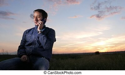 A young man sits at sunset and talks on his mobile phone. Beautiful sky behind.