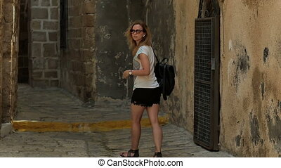 Female tourist walking exploring old streets. Slow motion....