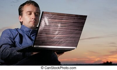 A young man is working behind a laptop at sunset. Beautiful...