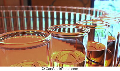 Ring of laboratory glass vials with yellow liquid. Chemical...