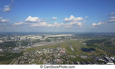 Scenic aerial shot of big commercial airplane taking off from international airport and flying by the camera