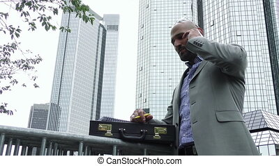 Man Talking with Cellphone in City and Business Tower