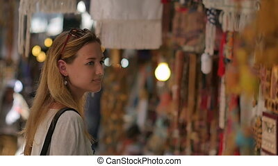 Young female tourist walking along old town market. Slow...