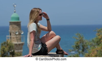 Young woman in sunglasses enjoying the sun and sea view....