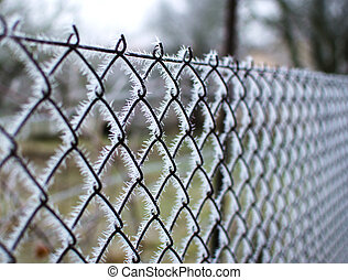 Close-up view of a wire fence with frost with ice crystals under a blue sky with a blurred background on a sunny winter day