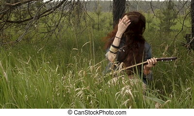 Hippie girl playing guitar on field - Pretty attractive...