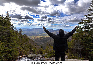 Man in praise looking out from elevation on Mount Washinton via Ammonoosuc ravine trail