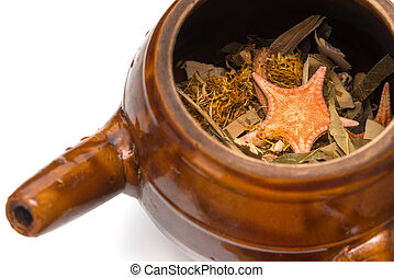 herbal in enamel pot on white background