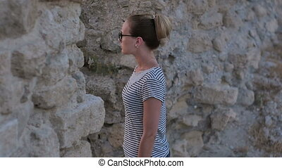 Young pretty woman looking at ancient ruins. Slow motion....