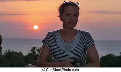 Young woman sitting near the sea and enjoying the sunset....
