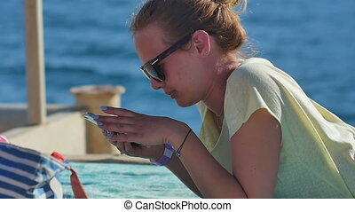 Young woman in sunglasses lying with smartphone on a beach....