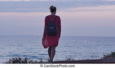 Young woman walking on seashore at dusk. Professional shot...