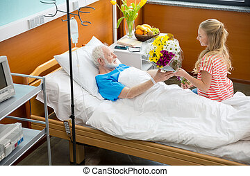 Grandfather and child in hospital - Smiling girl giving...