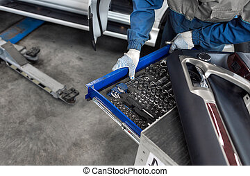 The mechanic selects the tool. tools for service station. spanners and socket nozzles