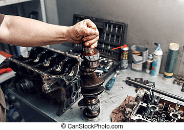 mechanic repairman at automobile car engine maintenance repair work. the crankshaft of the engine