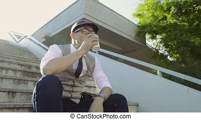 Mature businessman sitting on stairs in the city, drinking...