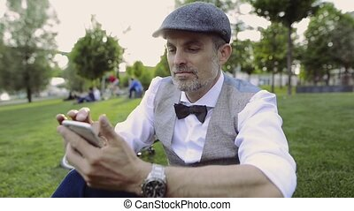 Mature businessman with smartphone and bicycle in city park....