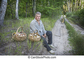 In summer, a man with two baskets of mushrooms is sitting in...
