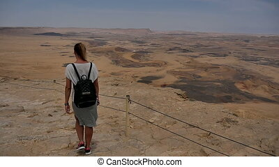 Female tourist with backpack walking along mountain rock...