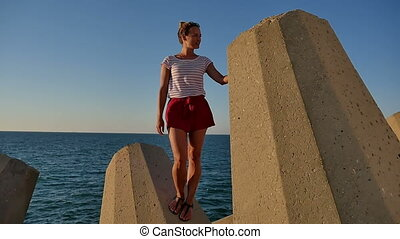 Smiling beautiful girl standing on concrete blocks in front...