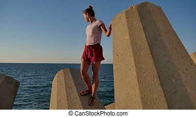Pretty girl standing on stony blocks looking at the sea....