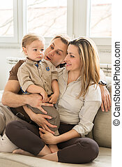 Portrait of happy parents sitting on the sofa with their beautiful baby boy. Family values.