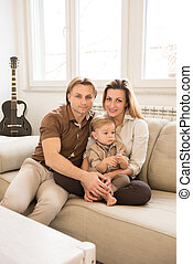 Happy parents sitting on the sofa with their beautiful baby boy.  Family values.