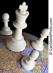 Chess pieces on an earth globe