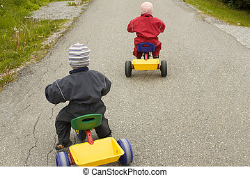 Children racing on tricycles, child in red leading in front...