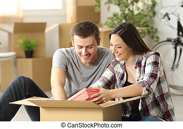 Couple unpacking moving house - Happy casual couple sitting...