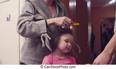 Young woman is combing girl's hair - A girl is sitting at a...
