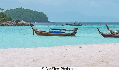 Long tail boats swinging in blue water with white sand beach...