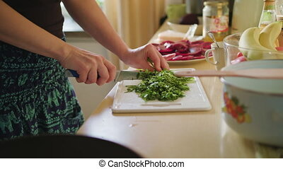 Woman Cuts Arugula Salad - Woman cuts arugula salad, the...