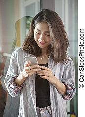 portrait of beautiful asian younger woman reading message in smart phone with smiling and happiness face