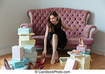 Happy young lady sitting on sofa choosing shoes. - Image of...
