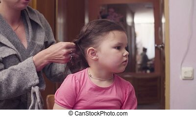 Young woman is combing girl's hair - A girl is sitting on a...