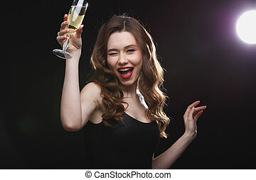 Cheerful beautiful young woman drinking champagne and...