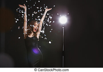 Cheerful young woman with raised hands dancing and having...