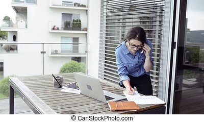 Woman on balcony working from home, making phone call. -...