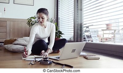 Woman with laptop at home working, writing into notebook. -...