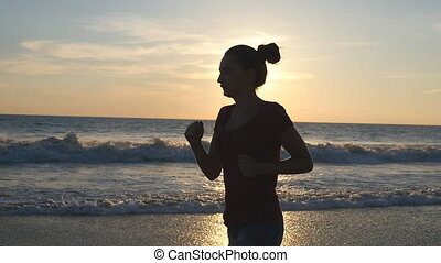 Silhouette of young woman running on sea beach at sunset. Girl jogging along ocean shore during sunrise. Female sportsman exercising outdoor. Healthy active workout lifestyle at nature. Slow motion
