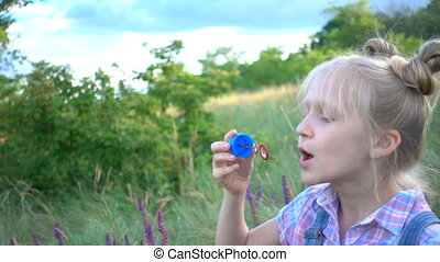 little girl blowing soap bubbles on a green lawn