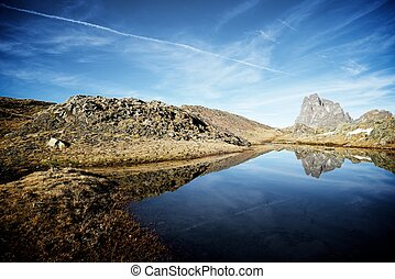 Pyrenees - Midi Dossau Peak reflected in a lake. Ossau...