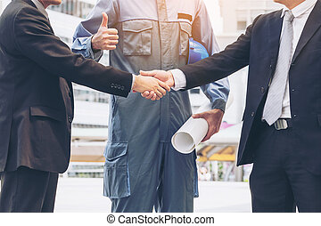 Businessmen handshake with engineer thumbs up - Business man...