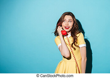 Attractive young girl in dress talking on retro telephone...