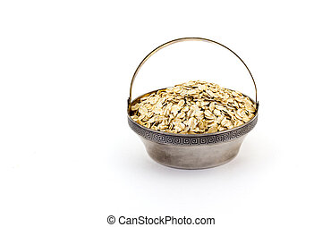 a silver bowl of uncooked rolled oats isolated on white background